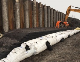 Installation of individual layers of soil bags with the insertion of geo reinforcement and backfilling